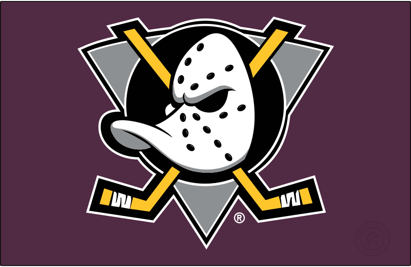 Mighty Ducks of Anaheim Logo Primary Dark Logo (1999/00-2005/06) - When used on a dark background, as it is shown here on purple, the original Mighty Ducks of Anaheim logo featured a duck-billed goalie mask on a grey (not jade) triangle, black circle, and two crossed hockey sticks. The Mighty Ducks used this logo from 1993 through 2006 but the shade of purple was lightened following the 1998-99 season. SportsLogos.Net