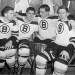 Boston Bruins (1954) Boston Bruins players Johnny Peirson, Fleming Mackell, Gordie Henry and Leo Labine in the dressing room wearing the Bruins white jersey in 1953-54