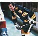 Boston Bruins (1976) Johnny Bucyk wearing the Boston Bruins black uniform with Massachusetts bi-centennial patch on shoulder during the 1975-76 season