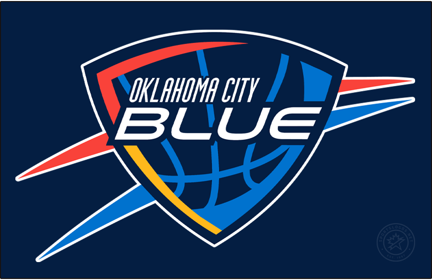 Oklahoma City Blue Logo Primary Dark Logo (2016/17-Pres) - The Oklahoma City Blue logo is designed to closely resemble that of their NBA affiliate the Oklahoma City Thunder. It features the team name in white italics on a navy blue shield, within the shield is a light blue basketball with sunset red and yellow shading. Outside the shield are sunset red and light blue streaks. The Blue dimmed the shade of red used on this logo in time for the 2016-17 season. SportsLogos.Net