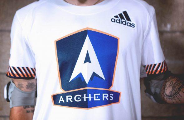 9aa38ee8705 The Archers logo jersey crest is a white arrowhead inside a two-toned blue  shield trimmed in orange